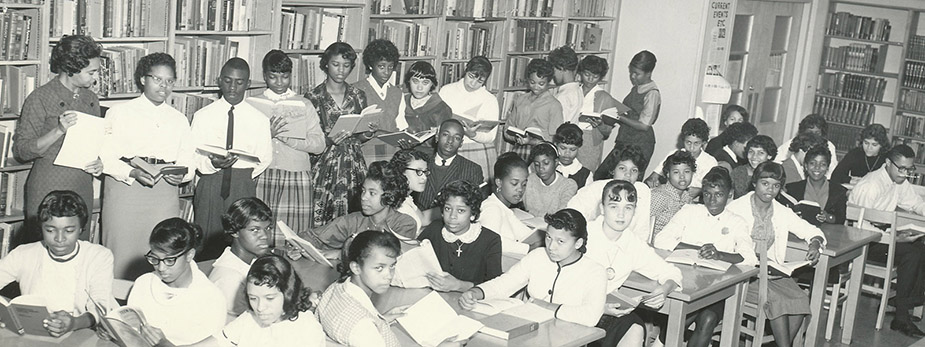 Black and white photograph of students in the school library.